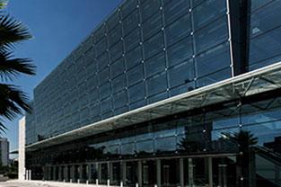 PRO MAGNO Centro de Eventos. Parte de fora mostrando com parte do céu azul e palmeira no lado esquerdo