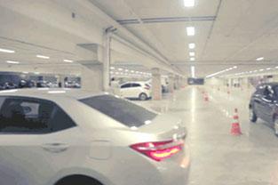 PRO MAGNO Centro de Eventos. Parte do estacionamento e parte de um carro prata no lado esquerdo