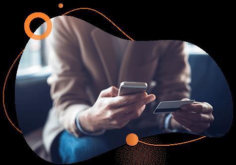 Pessoa sentada no sofá com celular e um cartão em suas mãos