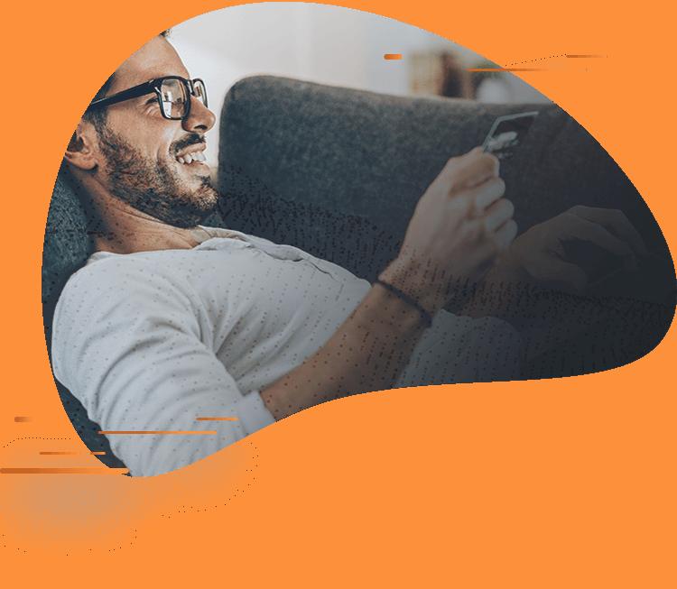 Homem de óculos, deitado num sofá, sorrindo