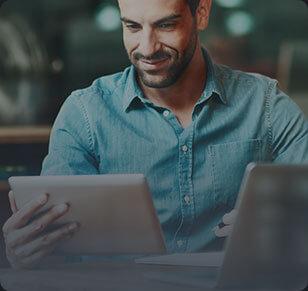Homem de camisa azul lendo algo em uma tablet