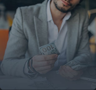 Homem de terno cinza segurando uma nota de 100 dólares