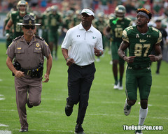 Coach Taggart runs on field with senior Adams before game