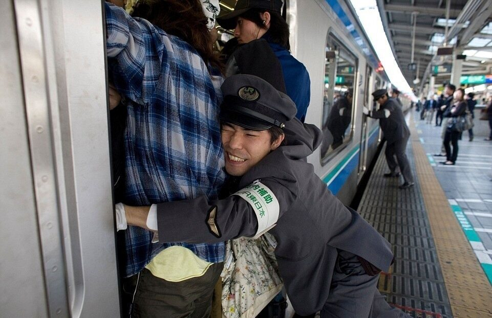 Men pushing people onto a train in Japan