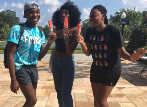 Three smiling African-American students with popsicles