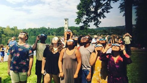 Group of students with solar eclipse glasses looking up at sky