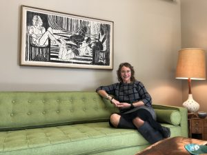 Caroline sitting on the green mid century modern sofa in her office.
