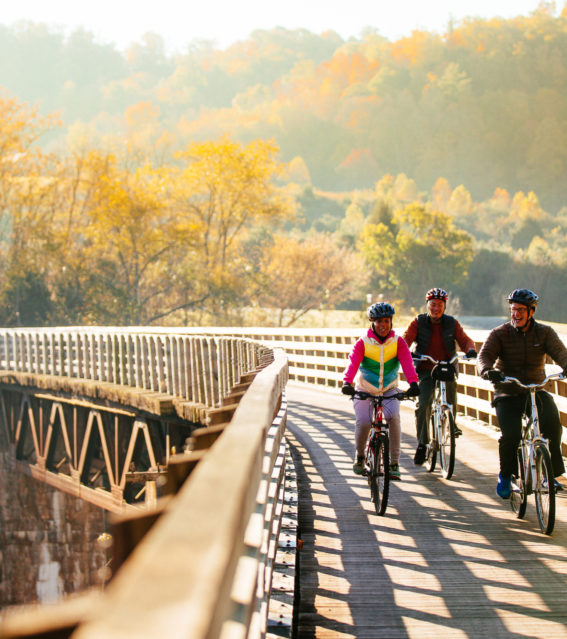 Virginia Creeper Trail bike riders on trestle in fall - horizontal - credit Sam Dean