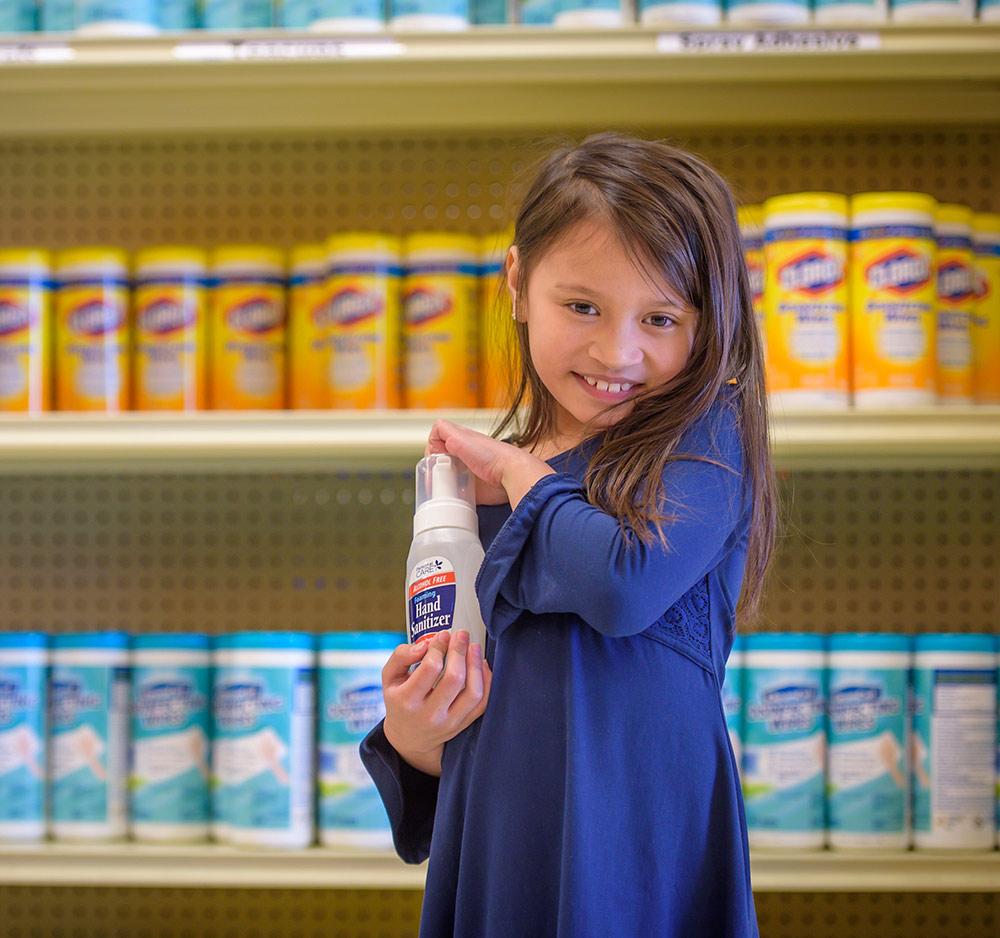 Girl holding bottle of cleaner.