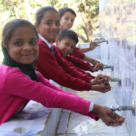 Children smiling and washing their hands.